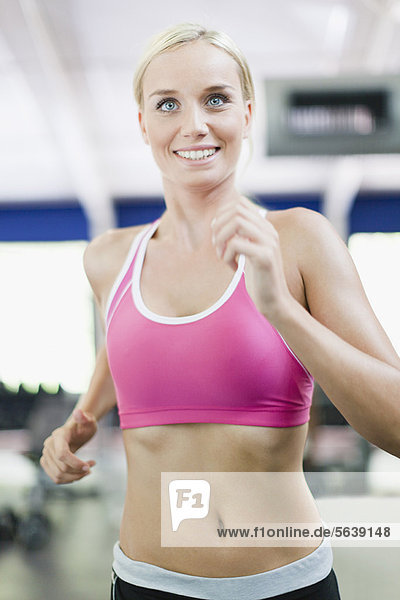 Woman using exercise machine in gym