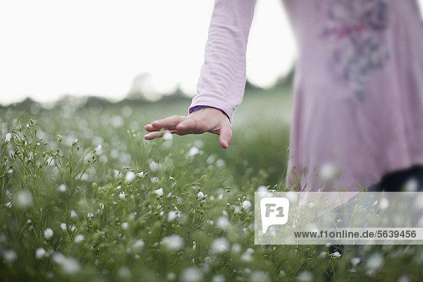 Mädchen beim Spaziergang im Blumenfeld