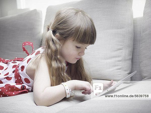 Girl using tablet computer on sofa