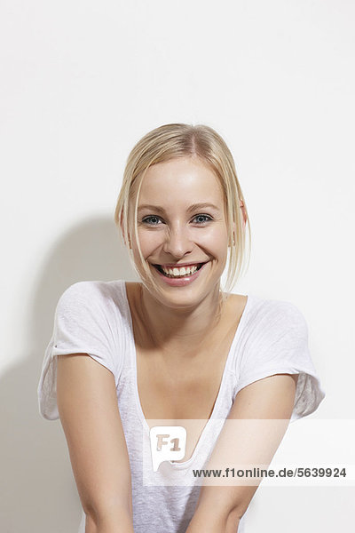 Lächelnde Frau  die sich an die Wand lehnt