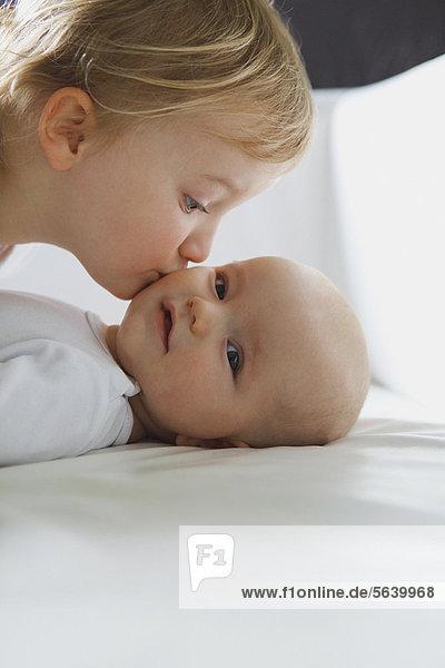 Mädchen küsst Geschwisterkind auf dem Bett