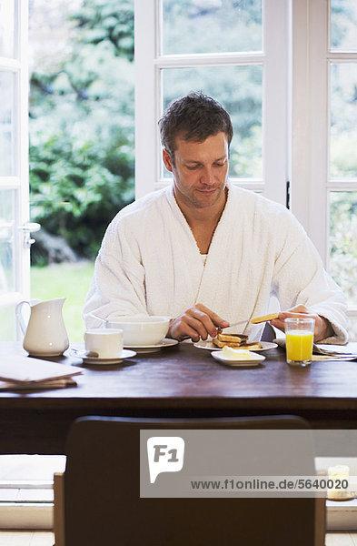Mann im Bademantel beim Frühstück