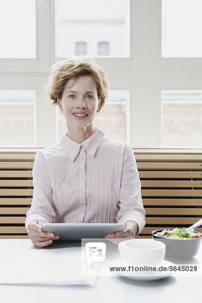 Eine Geschäftsfrau  die in der Mittagspause ein digitales Tablett benutzt.