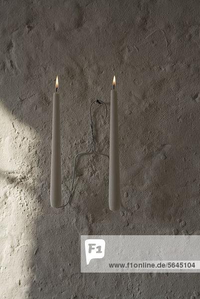 Entzündete Kerzen auf einem Kleiderbügel