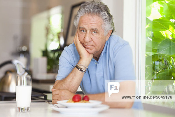Ein älterer Mann  der sich auf einen Tresen lehnt  mit seinem Frühstück darauf.