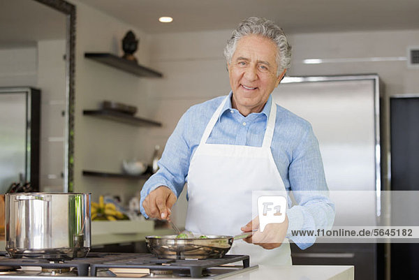 Ein fröhlicher Mann kocht in der heimischen Küche.