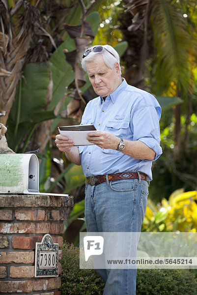 A senior man standing by his mailbox  looking at mail