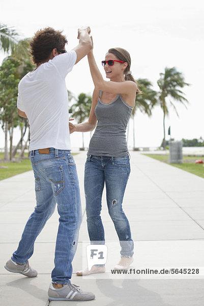 Junges Paar flirtet auf der Promenade