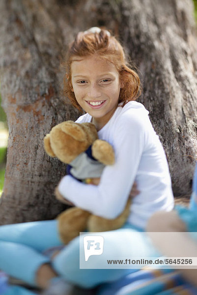 Mädchen umarmender Teddy neben Baum