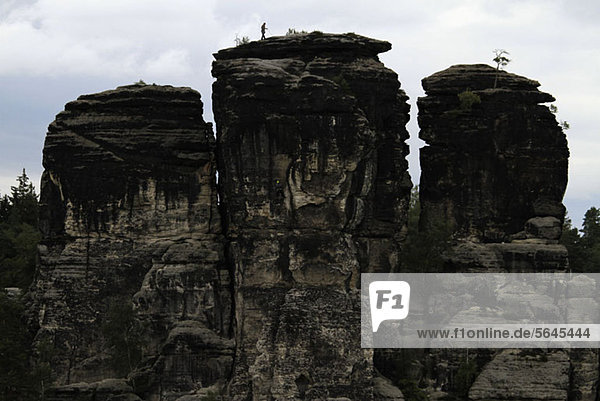 A person climbing a rock formation  Saxon Switzerland  Saxony  Germany