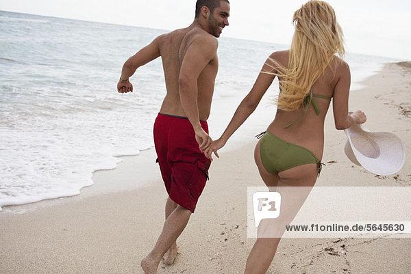Ein junges Paar  das Händchen hält und am Strand rennt.