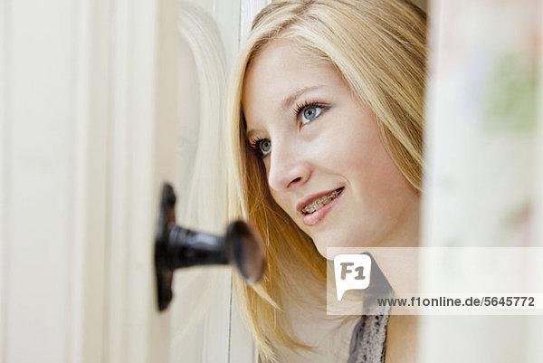 Ein Teenager-Mädchen  das aus dem Fenster schaut und träumt.