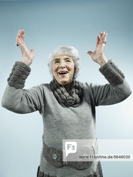 Eine ältere Frau mit erhobenen Armen zur Feier des Tages.