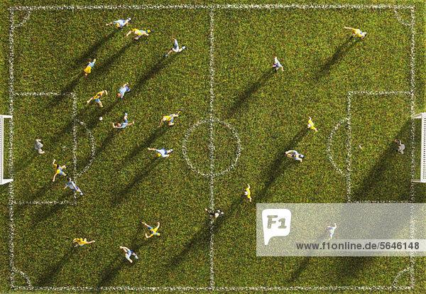Miniaturfiguren von zwei Fußballmannschaften  die ein Fußballspiel spielen  direkt darüber