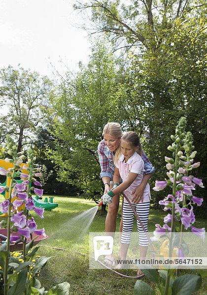 Mutter mit Tochter im Garten  Blumen gießen