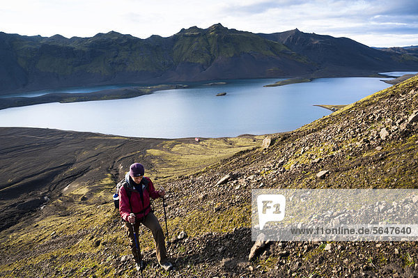 Hiker climbing Sveinstindur Mountain  overlooking Lake LangisjÛr  Highland  Iceland  Europe