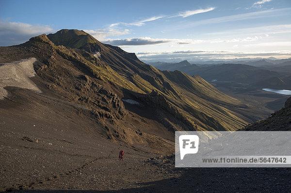 Wanderer besteigt den Berg Sveinstindur  Blick auf den See LangisjÛr  Hochland  Island  Europa
