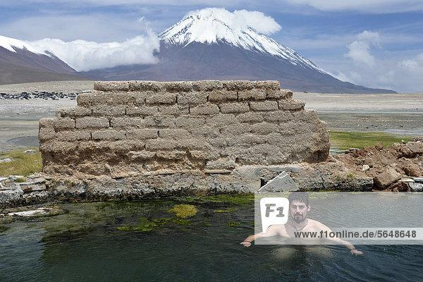 Tourist badet in heißer Quelle auf 4800m Höhe  Laguna Verde am Vulkan Licancabur  Altiplano  Dreiländereck Bolivien - Argentinien - Chile  Südamerika