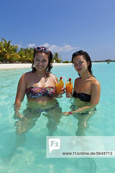 Zwei Mädchen  ca. 14 und 18 Jahre  mit Sonnenbrillen im Haar  trinken Cocktails in einer türkisfarbenen Lagune im Meer  hinten Malediveninsel  Malediven  Indischer Ozean  Asien