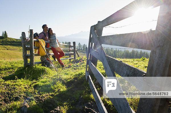 Österreich  Salzburg  Paar auf Holzbohle lehnend