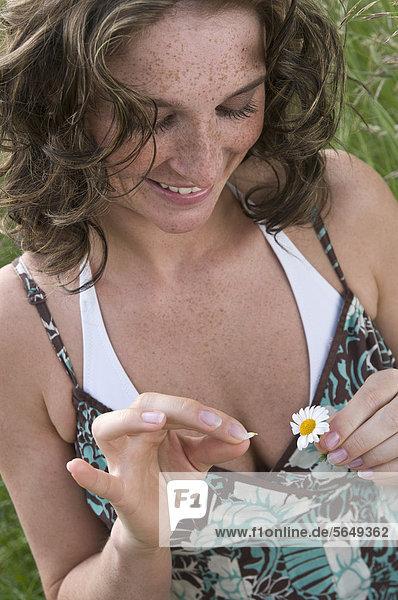 Deutschland  Nordrhein-Westfalen  Düsseldorf  Junge Frau pflückt Blütenblätter  lächelnd