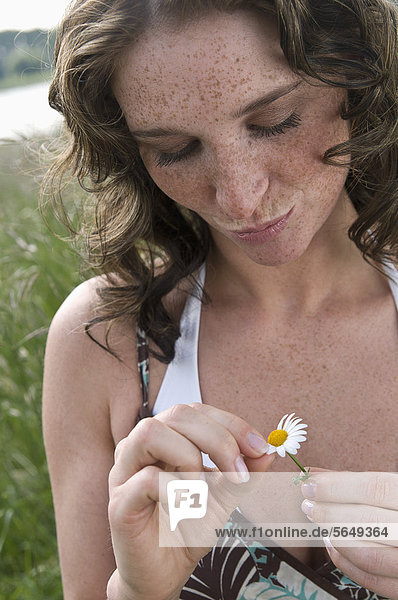 Germany  North Rhine Westphalia  Duesseldorf  Young woman plucking petals of flower