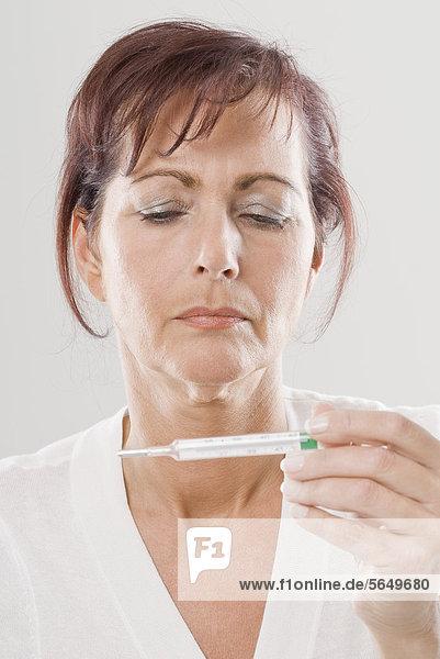 Reife Frau schaut auf Thermometer