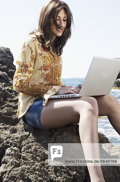 Spain  Mallorca  Young woman sitting on rock and using laptop at seaside