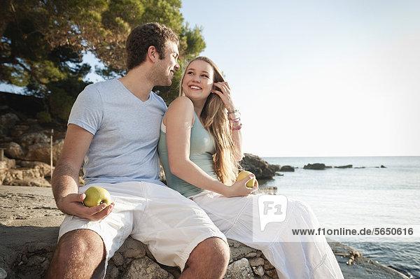 Spanien  Mallorca  Paar am Strand sitzend  lächelnd