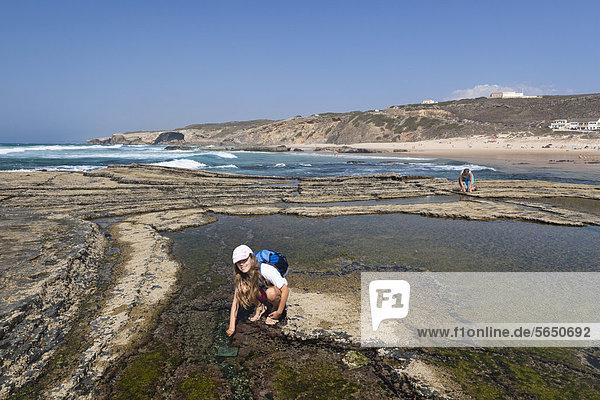 Girl playing on a tide pool  Monte Clerigo beach  Atlantic coast  Algarve  Portugal  Europe