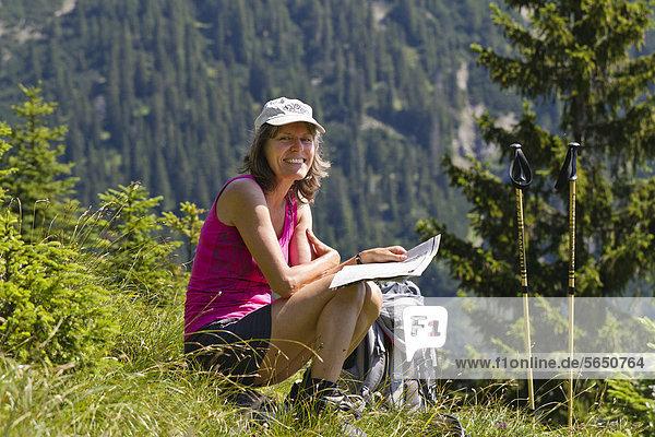 Frau studiert Wanderkarte im Gebirge  Bergwanderung  Bayerische Alpen  Oberbayern  Deutschland  Europa