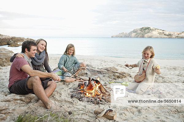 Spanien  Mallorca  Freunde beim Würstchengrillen am Lagerfeuer am Strand