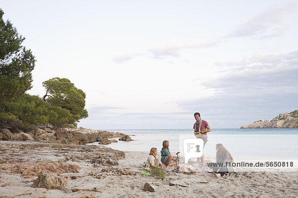 Spain  Mallorca  Friends at camp fire on beach