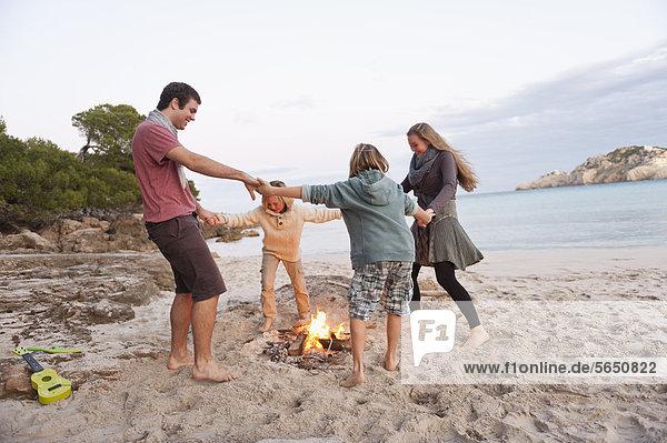 Spanien  Mallorca  Freunde tanzen am Lagerfeuer am Strand