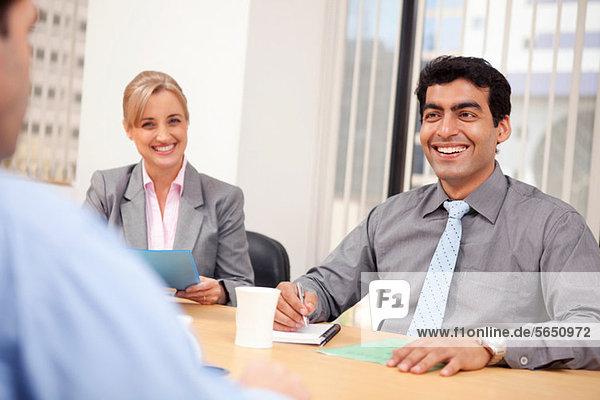 Geschäftsleute lächeln in einer Besprechung