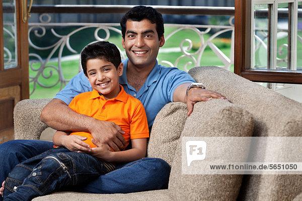 Porträt von Vater und Sohn auf einem Sofa