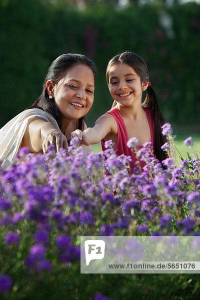 Mädchen und Großmutter schauen sich Blumen an