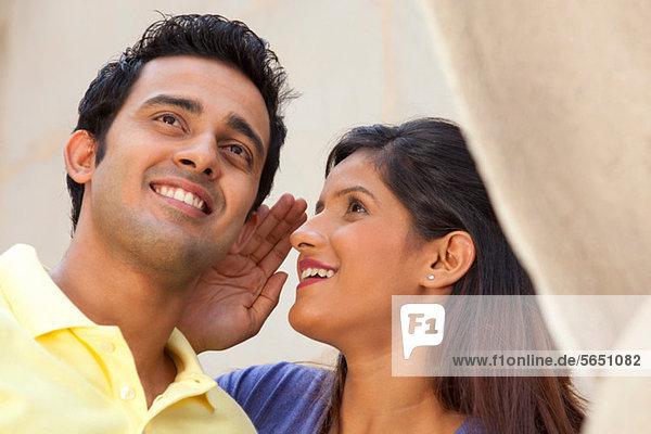 Frau flüstert einem Mann ins Ohr