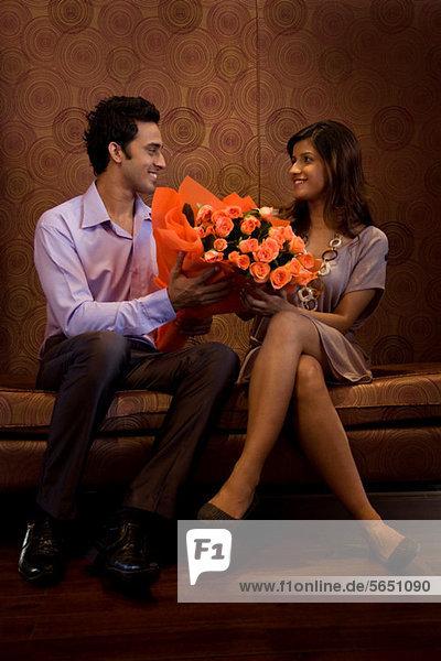Mann  der einer Frau einen Blumenstrauß schenkt.