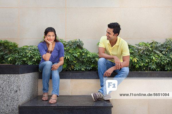 Paar sitzt draußen