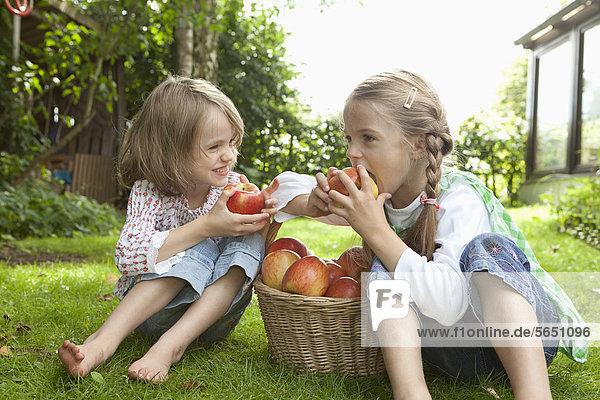 Girls eating apple in garden