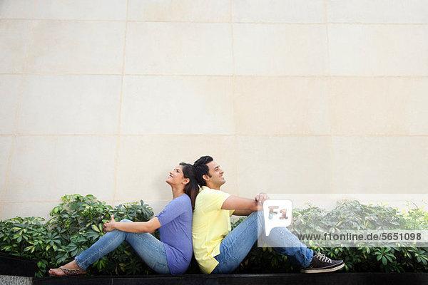 Paar sitzt Rücken an Rücken