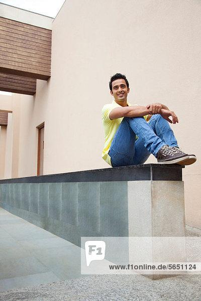 Mann auf einer Wand sitzend