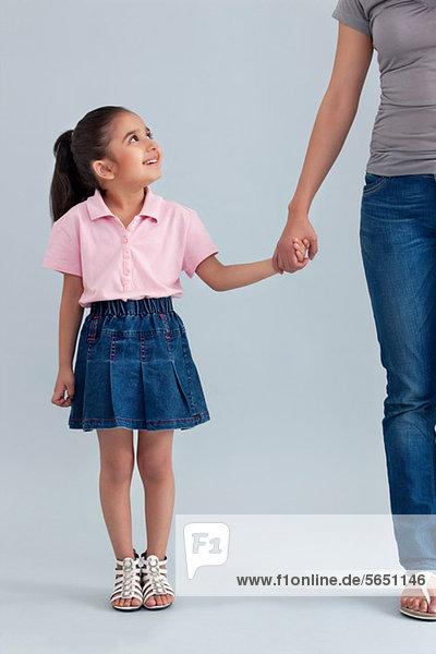 Junges Mädchen mit der Hand ihrer Mutter