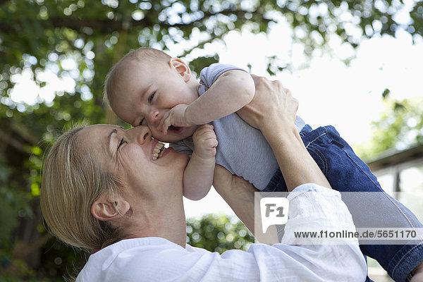 Mutter und kleiner Junge im Garten  lächelnd