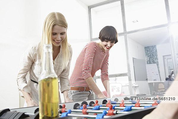 Junge Frauen spielen Tischfußball  lächeln