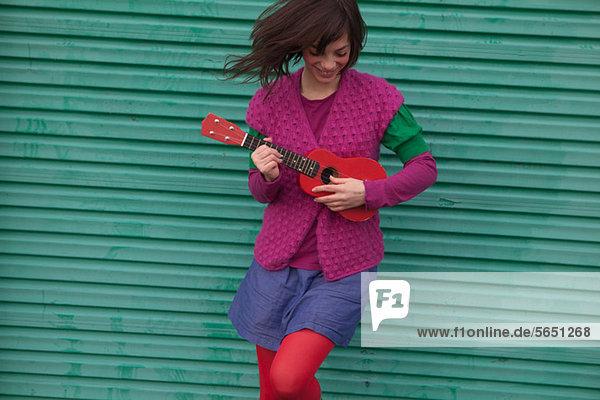 Junge Frau spielt Ukulelele