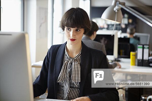 Männer und Frauen  die im Büro arbeiten