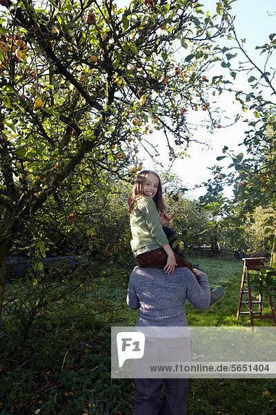 Mädchen auf der Mutter Schultern im Obstgarten