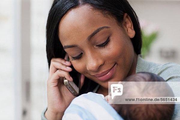 Mutter auf dem Handy mit ihrem Baby